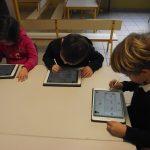 un groupe d'enfants étudie sur tablettes