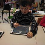 enfant apprenant à écrire grâce à une tablette