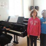 Deux enfants chantent accompagnés au piano
