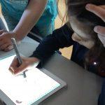 un enfant apprend l'écriture cursive sur tablette